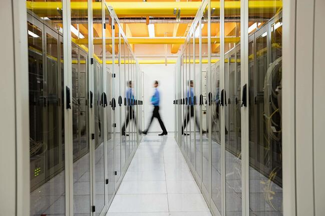 Man walking down a hall of servers